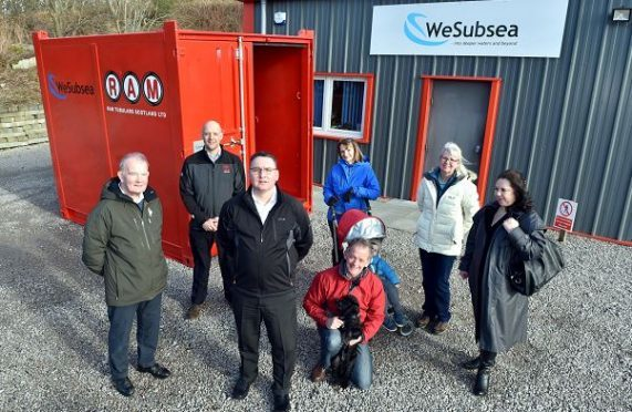 Wesubsea UK handed over a container to house Kemnay's flood defence equipment. Residents and members of the community council, (from left) Bob Ingram, Mark Mellor, RAM, Jason Wilson, Wesubsea, Gordon and Liz McKinstry with grandson Oliver, 2 and dog Kiera, Linda Kain and Irene Ferguson. Picture by Colin Rennie.