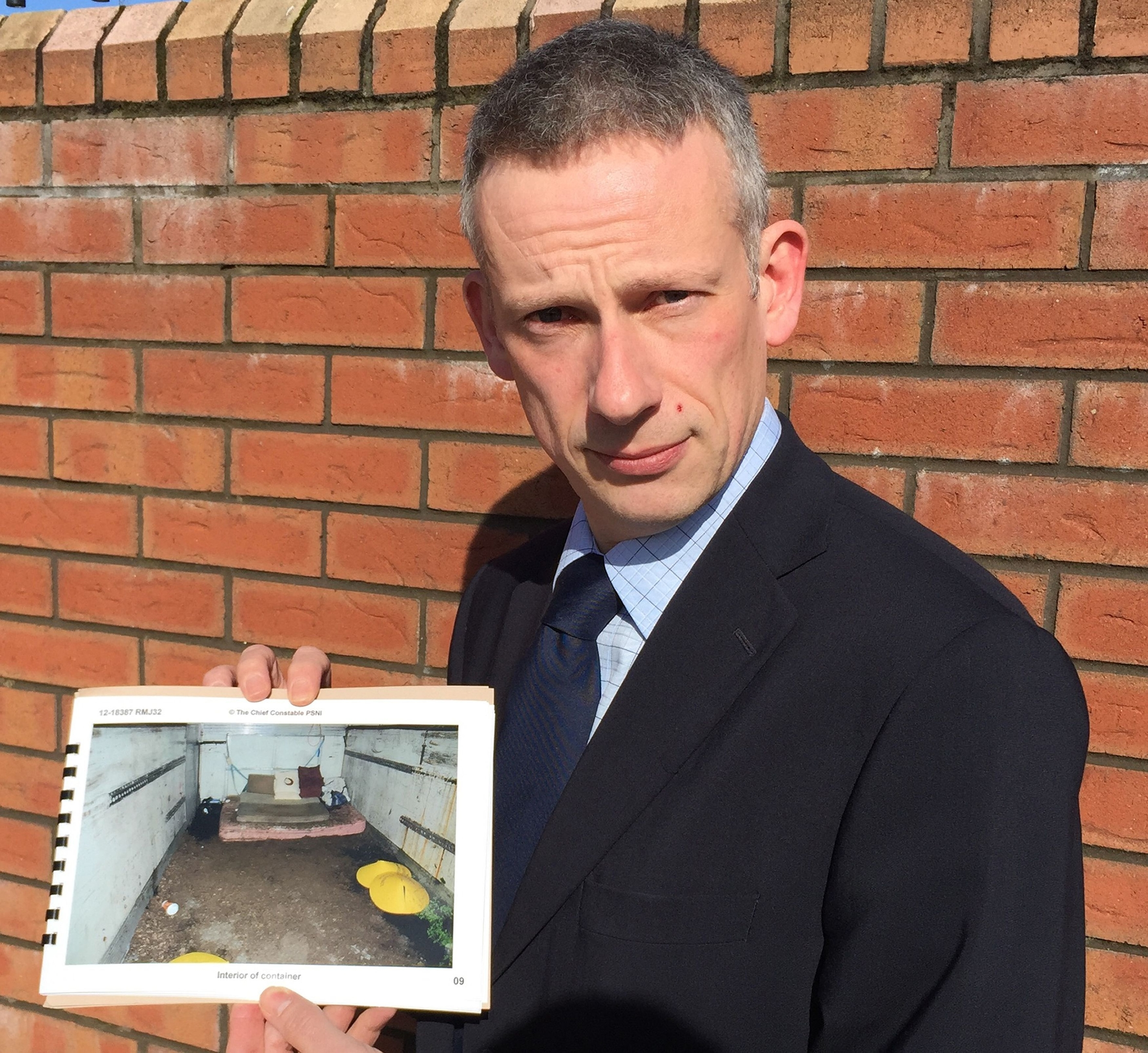 PSNI's Detective Chief Superintendent Raymond Murray holding a picture of squalid shipping container