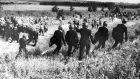 Police in anti-riot gear escort picketers away from their position near the Orgreave Coking Plant near Rotherham in 1984