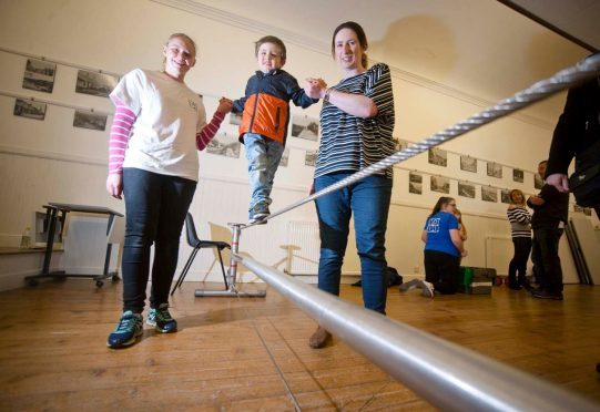 Callum Evans, 3, puts his balance to the test on the high wire with help from his mum Stephanie Evans, right, and workshop assistant Joanne Findlay.