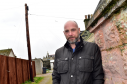 Macduff Scout chairman Colin Buist stands near the telegraph pole jeopardising the project