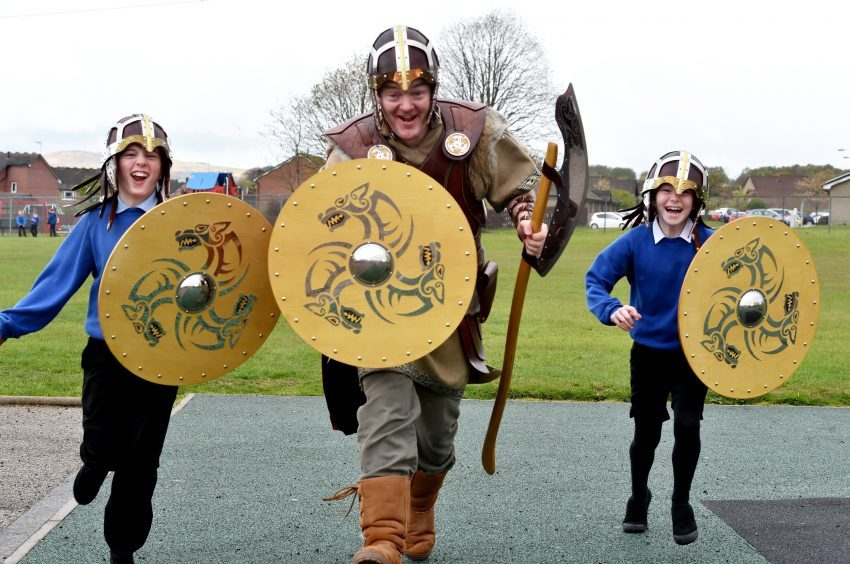 Pupils at Danestone School in Bridge of Don were visited by Kveldulf Bjalfason (known as Ulf) and his 25 strong Viking squad in full battle dress. Head teacher (who is in the squad) George Roberts with pupils Ben McDonald, 10 and Grace Grimley, 9. Pictures by Colin Rennie.