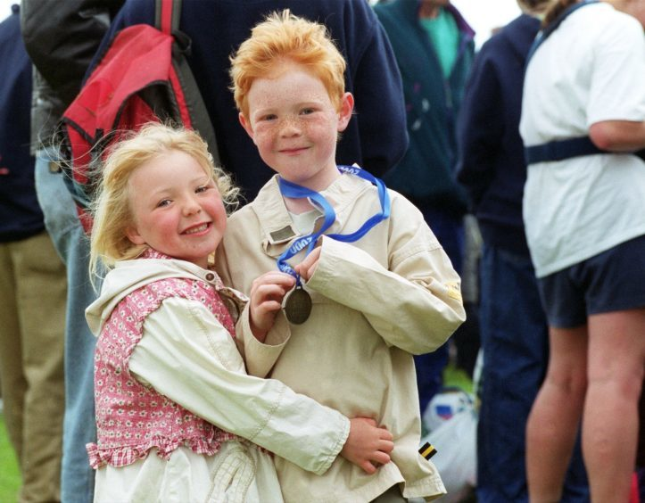 Seven-year-old Elloitt Griffiths  gets a cuddle from his sister Harriet,5, after running in the 1K race in 2000.