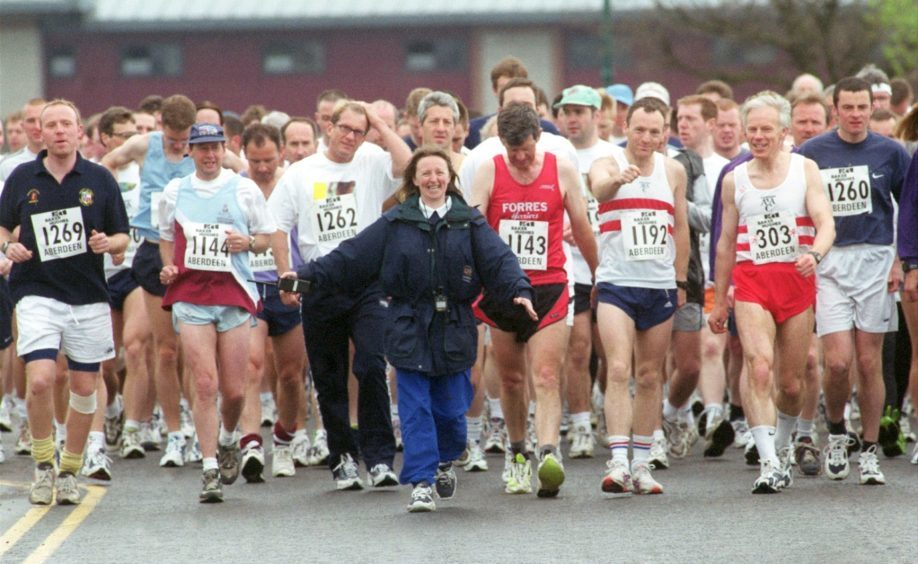 A steward gets the runners to the starting point of the Baker Hughes 10K race at the beach in 2000.