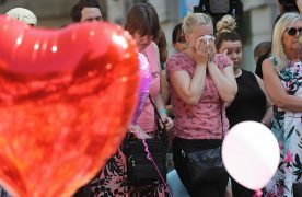 People look at tributes in St Ann's Square, Manchester, before a minute's silence to remember the victims of the terror attack