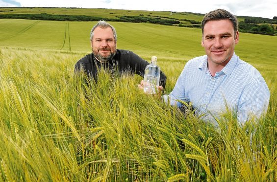 Stuart Wells and Ed Scaman with a bottle of their produce.