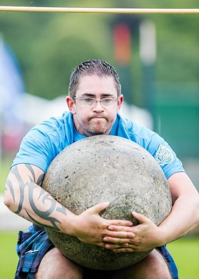 A competitor attempts to get the Inverness Stone over the bar at the Inverness Highland Games.