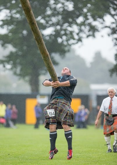 A competitor tosses the caber at the Inverness Highland Games.