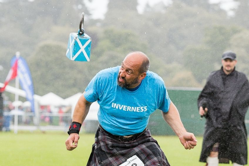 A competitor moves out of the way as the Weight Over the Bar comes down at the Inverness Highland Games.