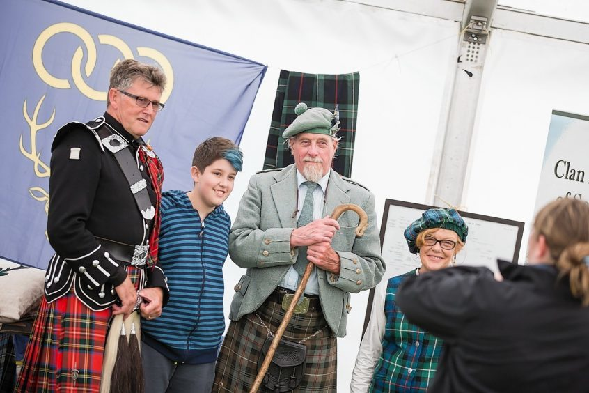 A young visitor poses with exhibitors at the Clan village at the Inverness Highland Games.