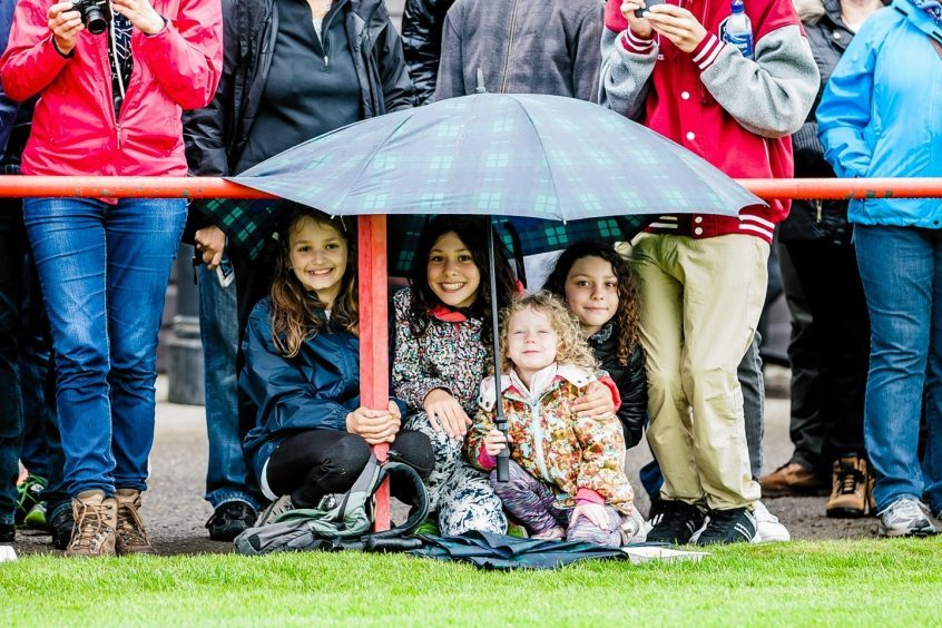 Young visitors take shelter to watch the events at the Inverness Highland Games.