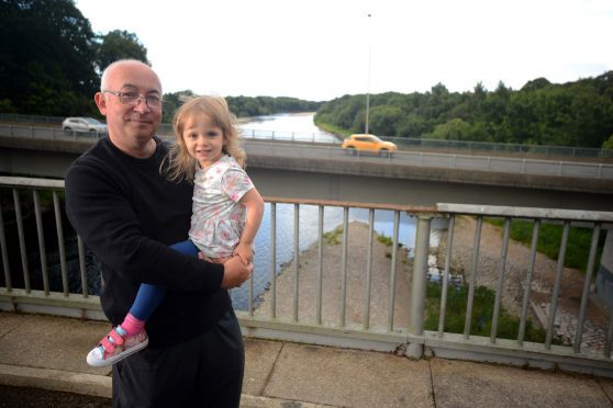 Cllr Marc MacRae at the Old Bridge over the Spey, next to the A96 at Fochabers with his 3 year old granddaughter, Emelia Stanforth.  Photo by Michael Traill						 9 South Road Rhynie Huntly AB54 4GA  Contact numbers Mob	07739 38 4792 Home	01464 861425