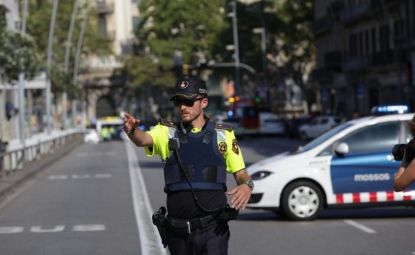 A policeman stands as he blocks the traffic after a van plowed into the crowd, injuring several people in Barcelona, Spain. (Photo by Albert Llop/Anadolu Agency/Getty Images)
