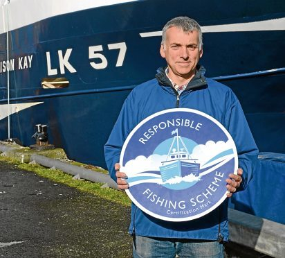 Skipper James Anderson with his boat, the Alison Kay in Scalloway harbour
