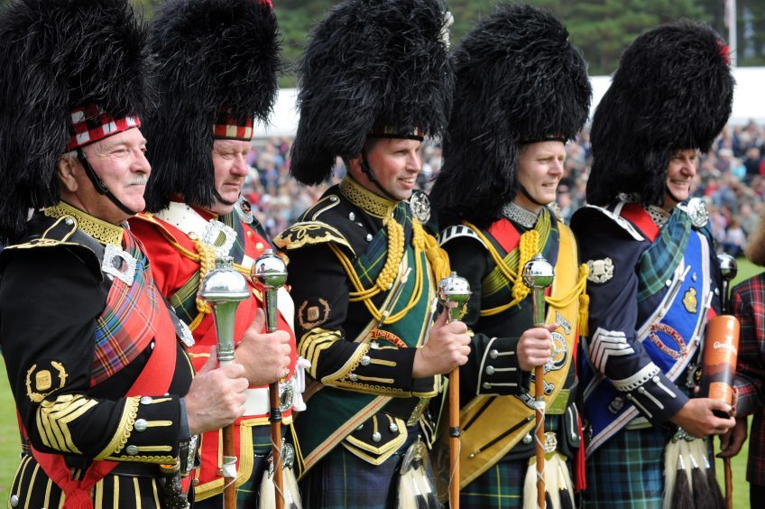 Pipe Majors line up after the mace twirling contest at the Braemar Gathering in 2010