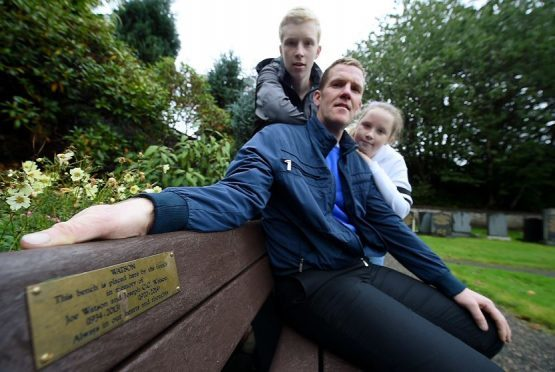 Fraser (seated) with his son Joe and daughter Amy on the Joe Watson bench in the graveyard.