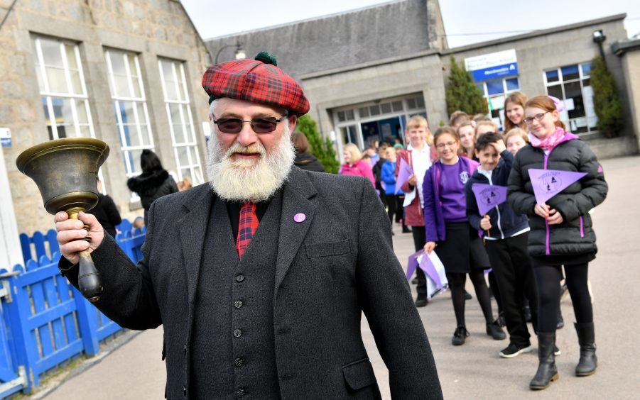 Janitor Michael Ross who rang the school bell for the last time leads the pupils out to Market Square.