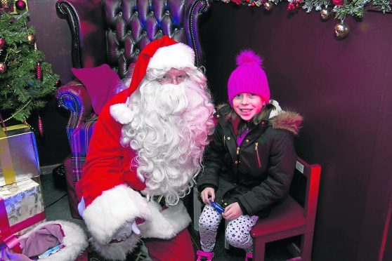 Young Jennifer Campbell Rockfield delivers her gift to santa for homeless and needy children.