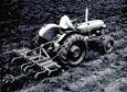 An early period photograph of a Fordson Dexta scrubbing down potatoes.