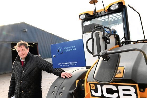 David Barron beside the JCB loader, which has been retrofitted with hydrolyser technology