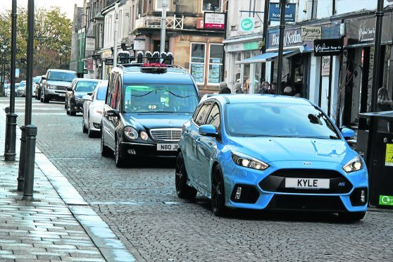 A car with Kyle's name on the name plate leads the hearse followed by 70 cars through Fort William high street