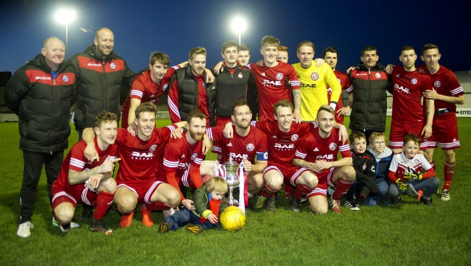 The Brora team celebrate with the cup.