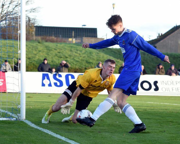 Cove's Sam Burnett makes keeper Ewan MacDonald save the ball.