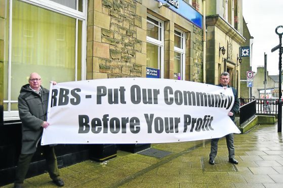 Councillors Glen Reynolds and Ross Cassie demonstrate outside the RBS in Banff