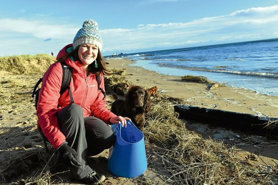 Marine biologist Lauren Smith, who also represents Aberdeen for Surfers Against Sewage, organises beach clean ups and is often helped by her spaniel Tattie.      Picture by Kami Thomson