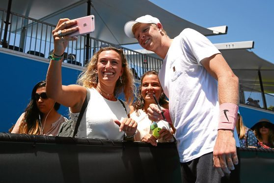 Kyle Edmund of Great Britain poses for photos with fans after completing a practice session on day 10 of the 2018 Australian Open at Melbourne Park