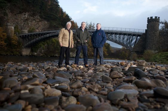 Campbell Croy, chairman of Friends of Craigellachie Bridge, Richard Lochhead MSP and Jock Anderson, trustee of Friends of Craigellachie Bridge, are eager to learn who owns the crossing.     Photo by Michael Traill 9 South Road Rhynie Huntly AB54 4GA  Contact numbers Mob07739 38 4792 Home01464 861425