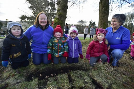 TURRIFF PRE SCHOOL PLAYGROUP CHILDREN (L TO R) ROBSON CHISHOLM, HARRISON SMITH, ALANA URQUHART AND JORJA DUNCAN PLANTING BULBS AT TURRIFF CEMETERY WITH FRIENDS MEMBERS MORAG LIGHTNING AND ANNETTE STEPHEN.