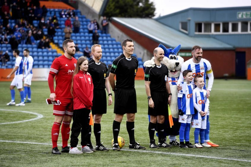 The captains pose with the match officials and mascots
