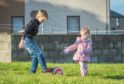 Noah Murray (left) and Lotte Cormack entertaining themselves with a football in absence of a playpark to play in. Picture by Jason Hedges.