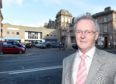 Councillor Allan Henderson, Chairman of HITRANS photographed in Station Square at the front of Inverness Railway Station.