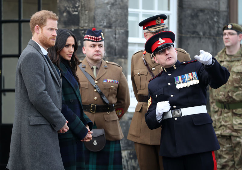 Prince Harry and Meghan Markle meet Sgt David Beveridge (right) before he fires the One o'clock gun at Edinburgh Castle