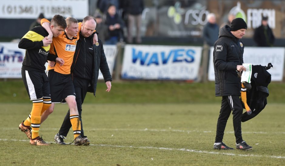 Battered and bruised - Fort William managers Ali Smoith and Paul MacLellan (right) with Ronan Cameron being helped off the field.