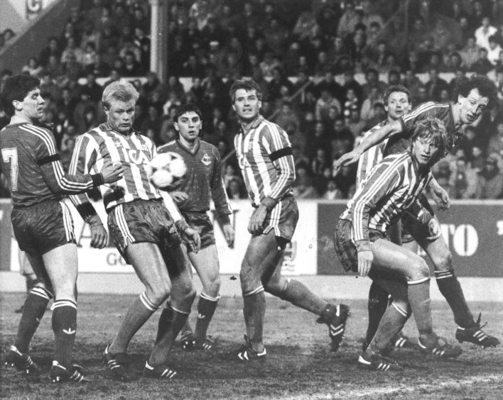 An anxious moment in the Gothenburg defence as this cross goes across the front of the goal. Dons players Stark, Hewitt and Black look on.