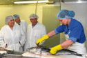 SCOTS TORY LEADER ANNABEL GOLDIE WITH LOCAL CANDIDATES GEORDIE BURNETT-STUART AND MICHAEL WATT WATCH KAREN SMITH FILLET A COLLIE AT CALEY FISHERIES DURING HER VISIT TO PETERHEAD.(BUCHAN/BROWN)