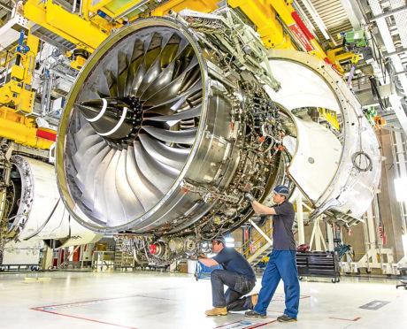 Technicians work on a Rolls-Royce Trent XWB engine.