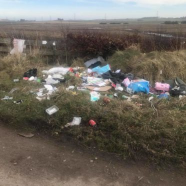 Piles of waste including food wrappers, cardboard boxes and black bags, have been left strewn near a track at Blackhills outside Peterhead.