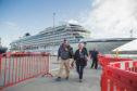 Tourists disembark from the cruise ship MV Columbus during her maiden call at Lerwick Harbour