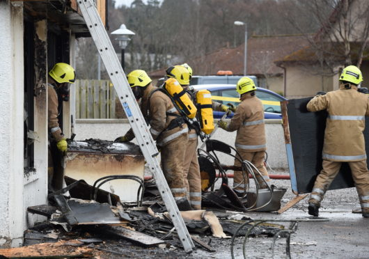 Fire crews remove equipment from the Forres Fish Bar.