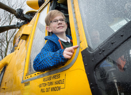 Calum Macpherson in the pilot seat of a Sea King helicopter.