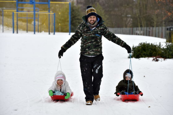 Colin Milne pulling Ella-Marie, 5, and Lachlan, 2, in sledges, at Duthie Park.