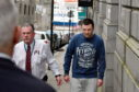 Mark Bruce is led away at court.