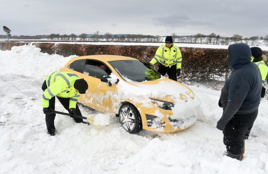 The snow storm continues in Easter Ross.   Police and farmers with heavy machinery recover cars and clear deep drifts on the road between Arabella and Hill of Fearn in Easter Ross.