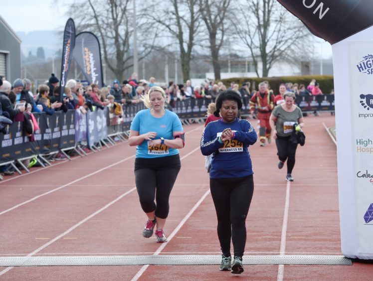 Runners cross the finish line in the 5k fun Run.