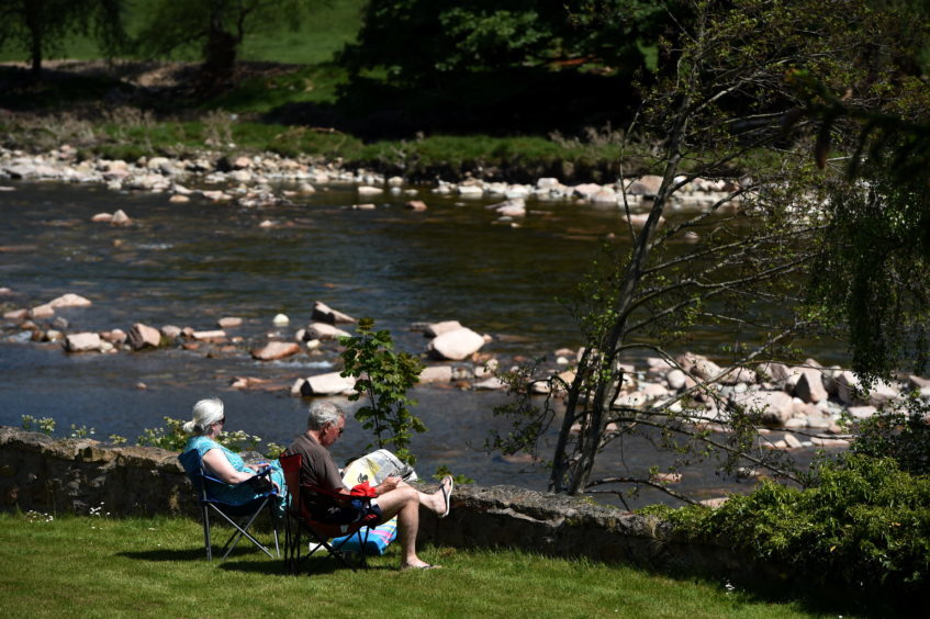 Tourists enjoying the sun on the banks of the River Dee