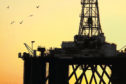 Silhouette of an oil rig       sun rising setting generic black gold offshore birds platform